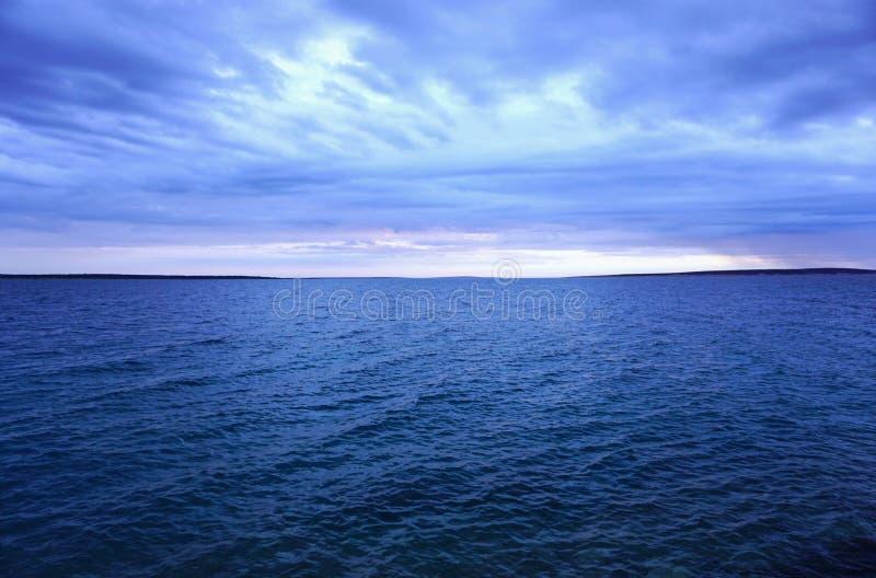 Σκούρο μπλε νεφελώδης ουρανός και μεγάλα θαλάσσια βάθη μετά από τη θύελλα με τη διαδρομή του ηλιοβασιλέματος στον ορίζοντα στοκ φωτογραφίες
