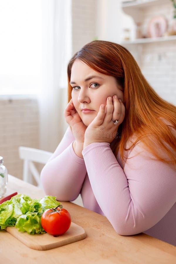 Σκυθρωπή παχουλή γυναίκα που σκέφτεται για τη διατροφή της στοκ εικόνες