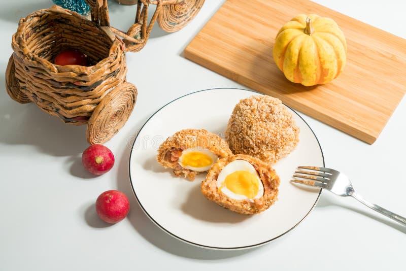 Σκωτσέζικα αυγά με το διακοσμημένο υπόβαθρο στοκ εικόνα