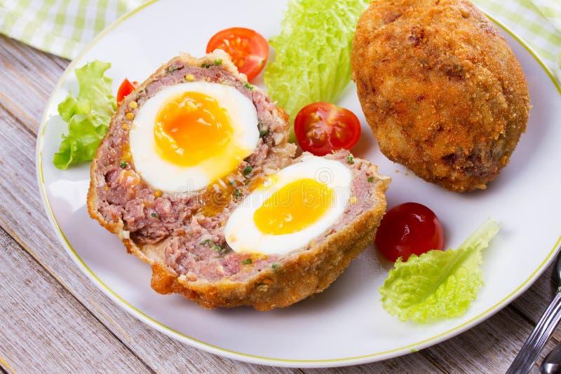 Σκωτσέζικα αυγά που εξυπηρετούνται με το κεράσι και τη σαλάτα ντοματών στο άσπρο πιάτο στοκ εικόνα με δικαίωμα ελεύθερης χρήσης