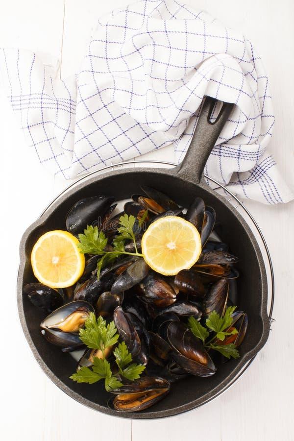 Σκωτσέζικα μύδια με το μαϊντανό και το λεμόνι σε ένα τηγάνι χυτοσιδήρου στοκ εικόνες