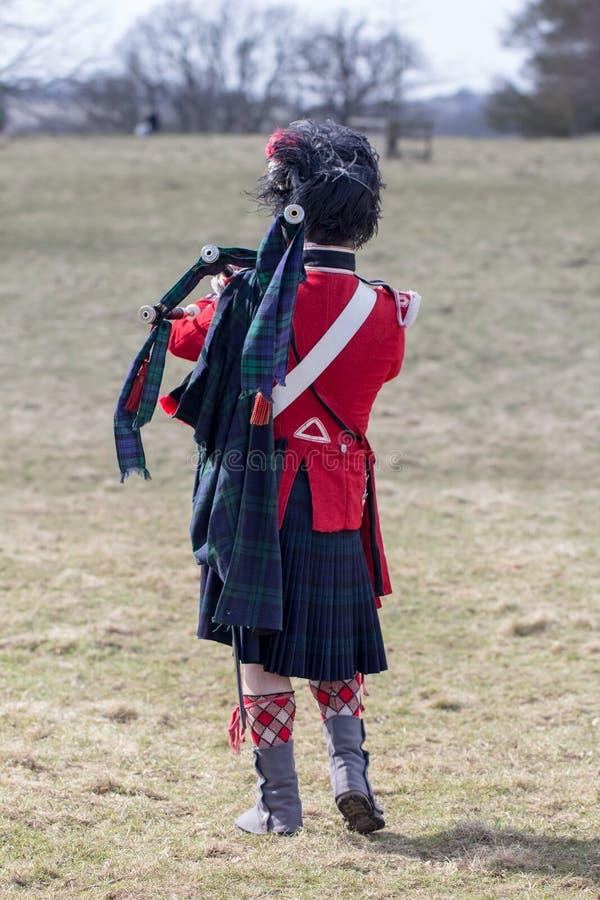 Σκωτσέζικος αυλητής φρουρών στον τομέα με τα bagpipes στοκ φωτογραφία