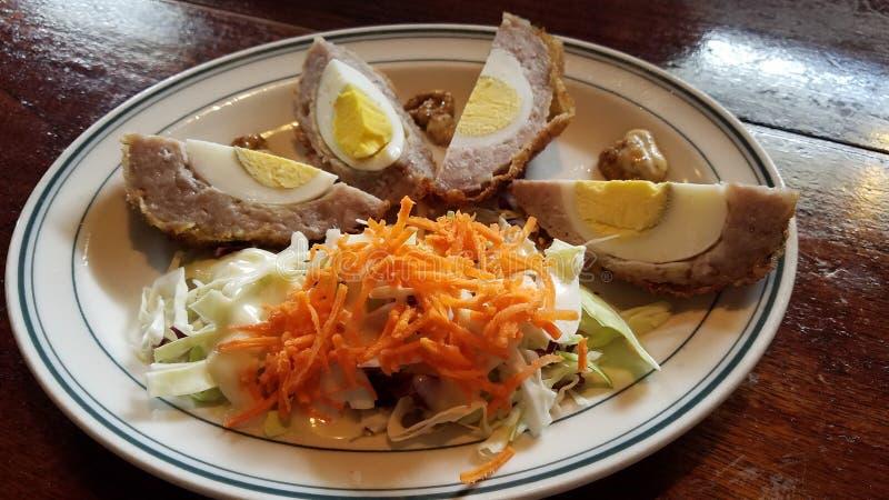 Σκωτσέζικο κρέας λουκάνικων τροφίμων με τα αυγά και τη σαλάτα καρότων στοκ εικόνα με δικαίωμα ελεύθερης χρήσης