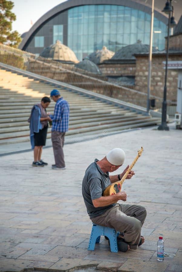 ΣΚΌΠΙΑ, 29,2018 ΜΑΚΕΔΟΝΊΑ-ΑΥΓΟΥΣΤΟΥ: Busker με το παραδοσιακό αλβανικό όργανο στοκ φωτογραφία με δικαίωμα ελεύθερης χρήσης