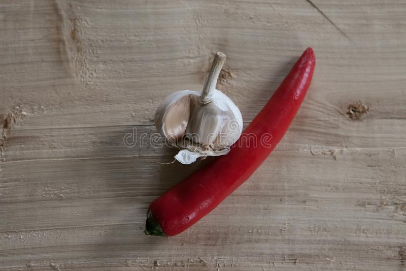Σκόρδο και τσίλι σε ένα κομμάτι του ξύλου στοκ εικόνες