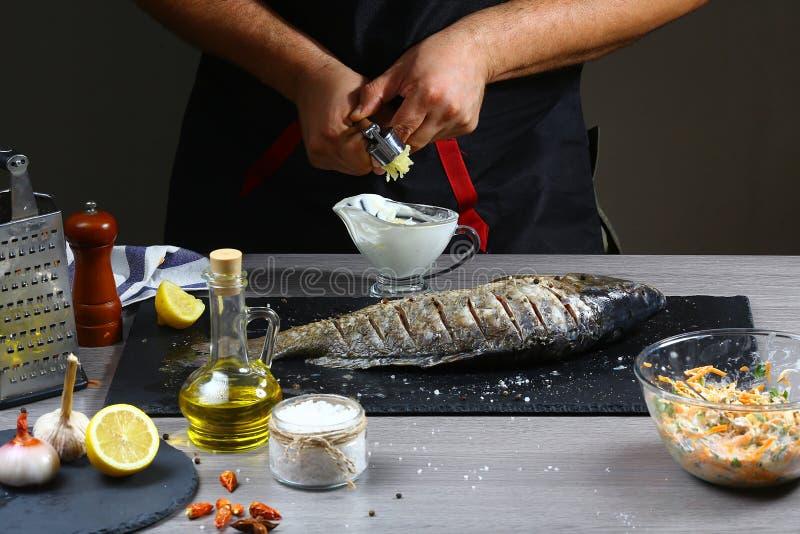 Σκόρδο συμπιέσεων αρχιμαγείρων της κατασκευής της σάλτσας ψαριών Παραδίδει τη διαδικασία τα ψάρια Τοπ άποψη, θέση για το κείμενο στοκ εικόνες