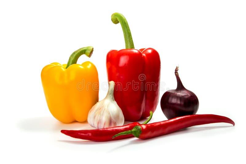 Σκόρδο, κρεμμύδι, πράσινο και κόκκινο τσίλι πιπεριών κουδουνιών, που απομονώνονται στο λευκό στοκ φωτογραφία