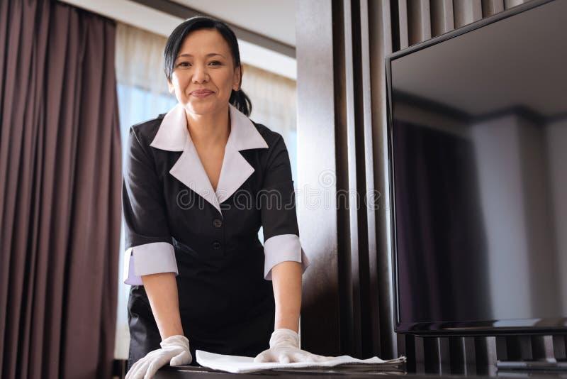 Σκληρά εργαζόμενο ασιατικό κορίτσι ξενοδοχείων που σκουπίζει τη σκόνη στοκ φωτογραφίες με δικαίωμα ελεύθερης χρήσης