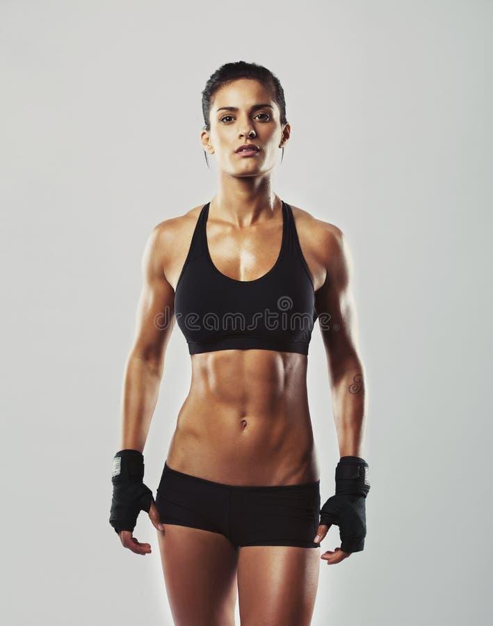 Σκληρή νέα γυναίκα με το μυϊκό σώμα στοκ φωτογραφία με δικαίωμα ελεύθερης χρήσης