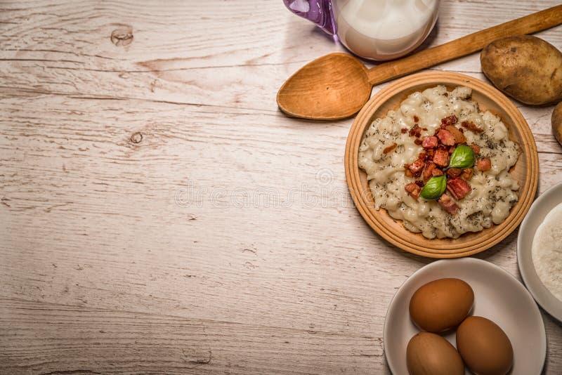 Σλοβάκικο παραδοσιακό gnocchi πατατών πιάτων με το τυρί προβάτων ` s, σε έναν ξύλινο πίνακα που τοποθετούνται στον πίνακα στοκ φωτογραφίες