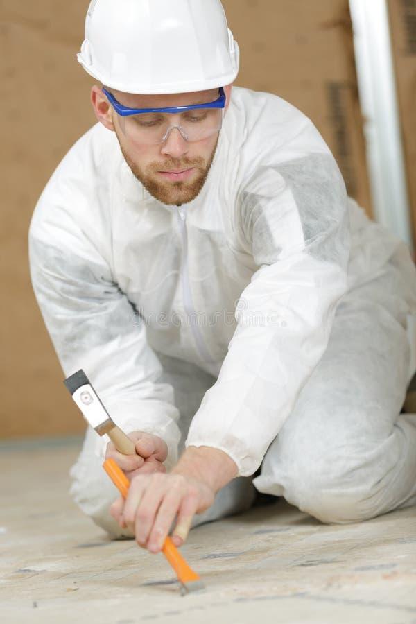 Σμίλευση εργαζομένων στα κεραμίδια πατωμάτων στοκ εικόνες