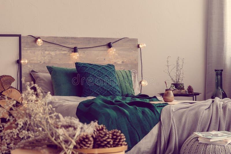Σμαραγδωτά πράσινα μαξιλάρια και κουβέρτα σε ξύλινα κρεβάτια με μέγεθος βασιλιά στοκ εικόνες