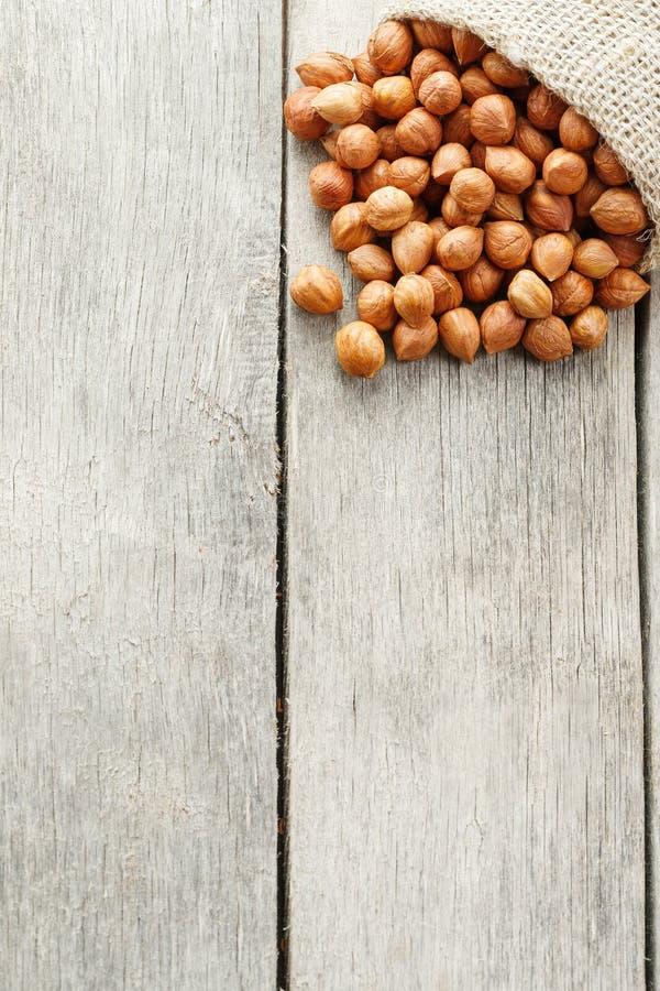 Σμιλευμένα φουντούκια σε μια τσάντα burlap σε έναν γκρίζο ξύλινο πίνακα Φρέσκος που συγκομίζεται οργανικός στοκ φωτογραφία με δικαίωμα ελεύθερης χρήσης