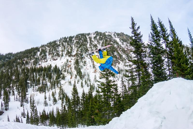 Σνόουμπορντερ πιο ελεύθερος πηδώντας από μια χιονοστιβάδα στον ήλιο σε ένα φόντο δάσους και βουνών στοκ εικόνες