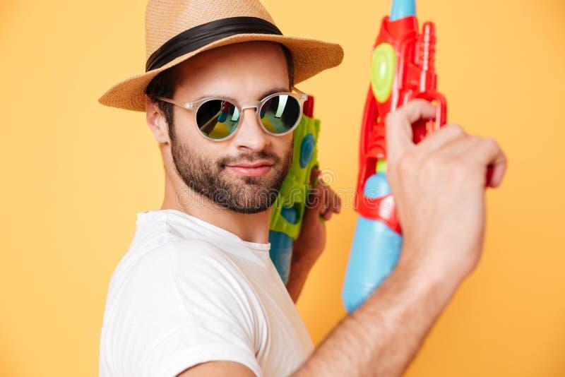 Σοβαρά πυροβόλα όπλα νερού παιχνιδιών εκμετάλλευσης νεαρών άνδρων στοκ εικόνες