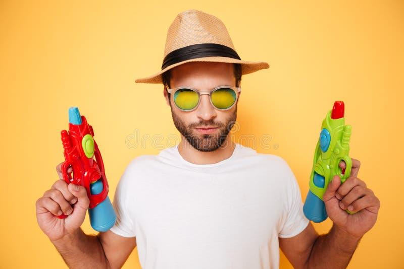 Σοβαρά πυροβόλα όπλα νερού παιχνιδιών εκμετάλλευσης νεαρών άνδρων στοκ φωτογραφία με δικαίωμα ελεύθερης χρήσης