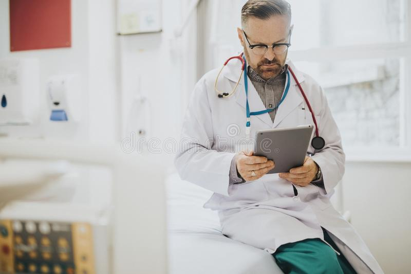 Σοβαρή ανάγνωση γιατρών από μια ταμπλέτα στοκ φωτογραφία με δικαίωμα ελεύθερης χρήσης
