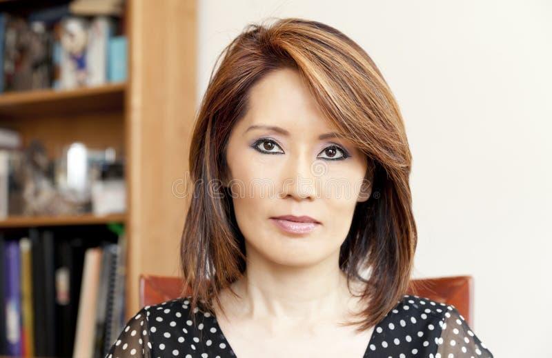 Σοβαρή ασιατική γυναίκα στο γραφείο της στοκ φωτογραφίες