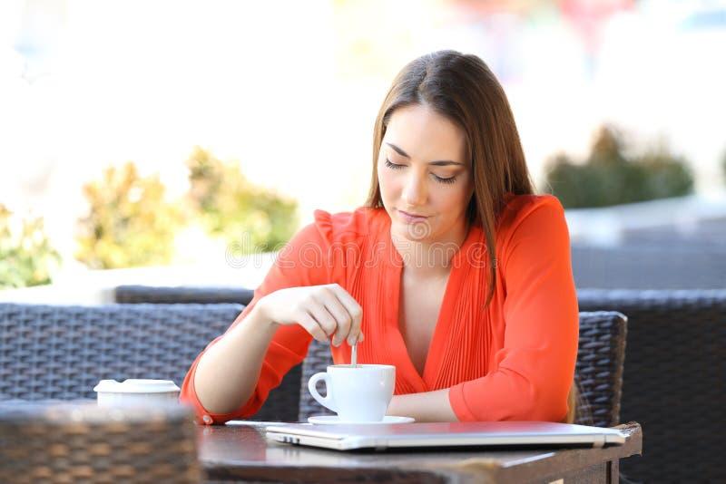 Σοβαρή γυναίκα σε μια καφετερία που ανακατώνει το ποτό στοκ εικόνα