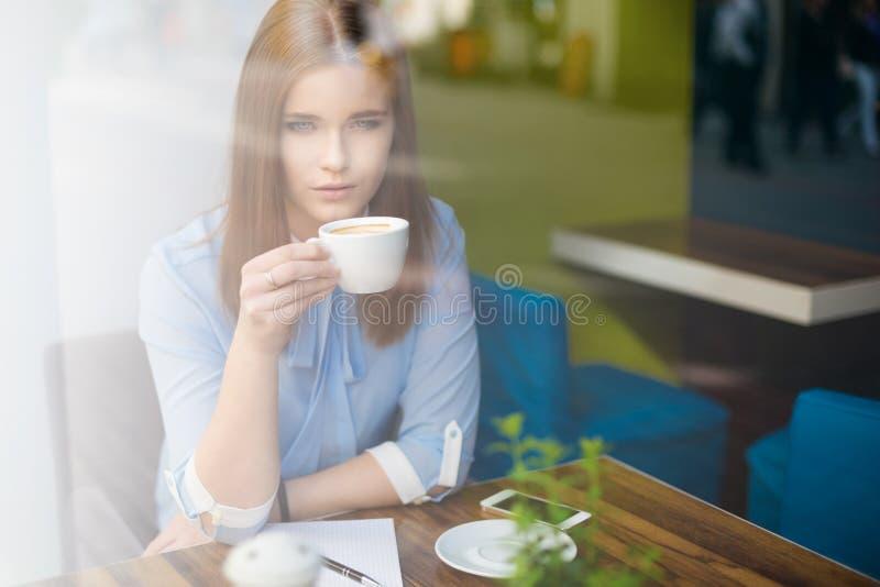 Σοβαρή γυναίκα στη καφετερία στοκ εικόνα