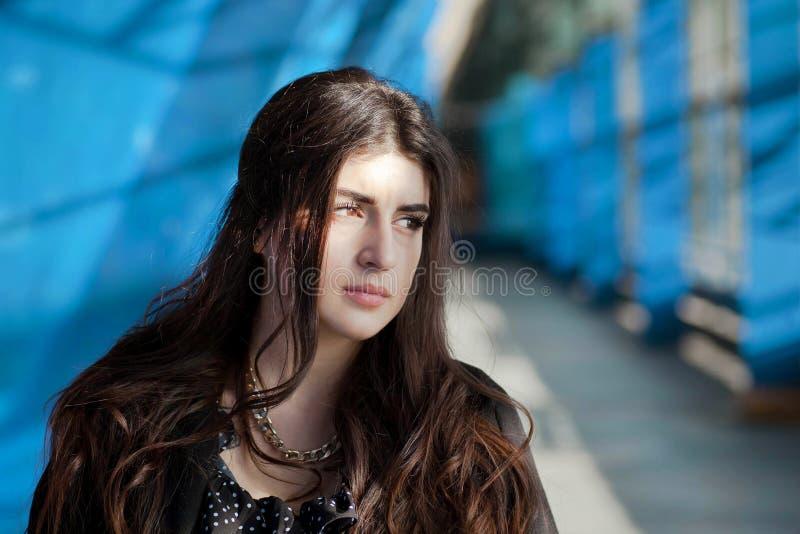 Σοβαρή γυναίκα brunette που στέκεται κάτω από τους μπλε τοίχους χρώματος τ στοκ εικόνες με δικαίωμα ελεύθερης χρήσης