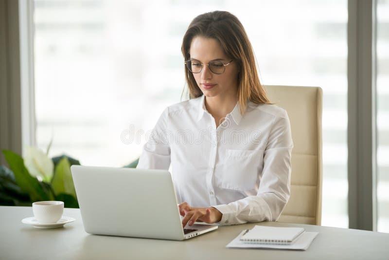 Σοβαρή επιχειρηματίας που χρησιμοποιεί το επιχειρησιακό λογισμικό υπολογιστών που κάθεται το α στοκ φωτογραφίες