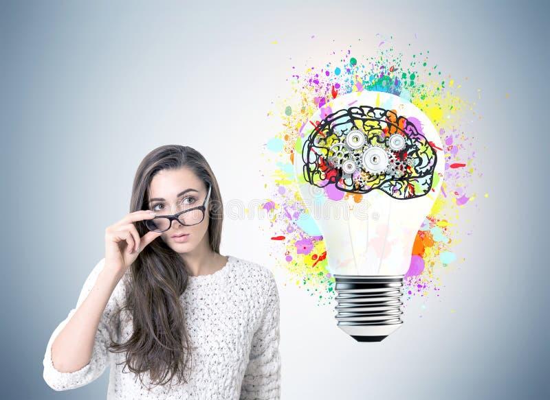 Σοβαρή επιχειρηματίας στα γυαλιά, εγκέφαλος βαραίνω, βολβός στοκ φωτογραφία με δικαίωμα ελεύθερης χρήσης