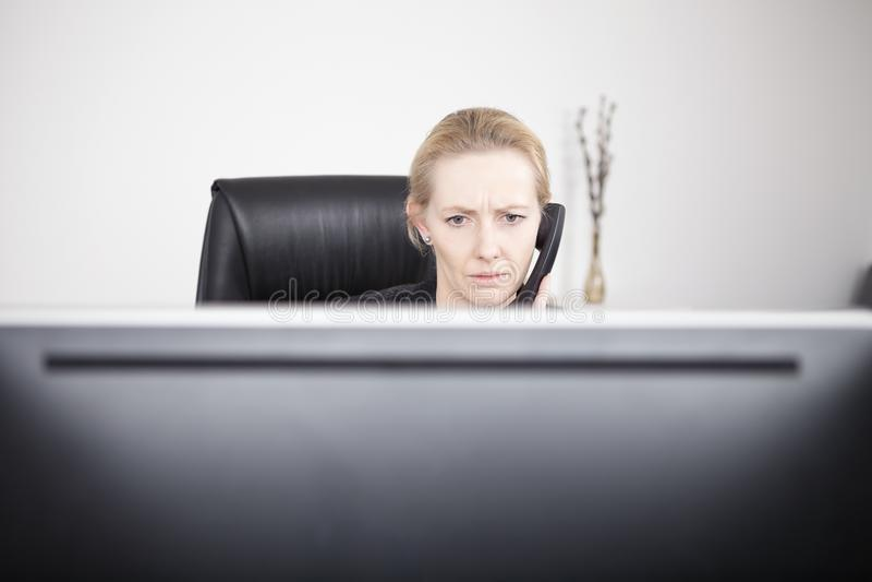 Σοβαρή επιχειρηματίας στο τηλέφωνο που εξετάζει το όργανο ελέγχου στοκ φωτογραφία