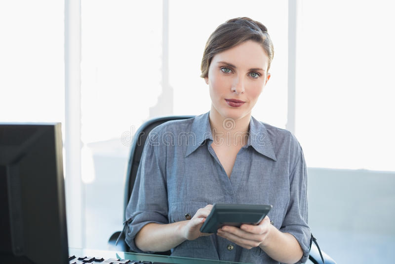 Σοβαρή ελκυστική επιχειρηματίας που κρατά μια συνεδρίαση υπολογιστών στο γραφείο της στοκ φωτογραφία με δικαίωμα ελεύθερης χρήσης