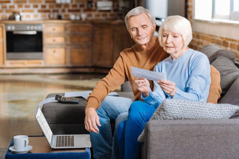Σοβαρή ηλικιωμένη γυναίκα που ελέγχει τα οικονομικά έγγραφα στοκ εικόνες