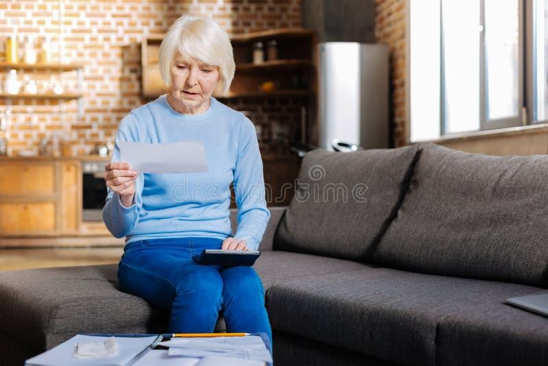 Σοβαρή ηλικιωμένη γυναίκα που χρησιμοποιεί έναν υπολογιστή στοκ φωτογραφίες