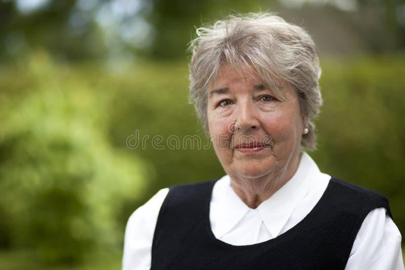 Σοβαρή ηλικιωμένη γυναίκα που εξετάζει τη κάμερα στοκ εικόνες