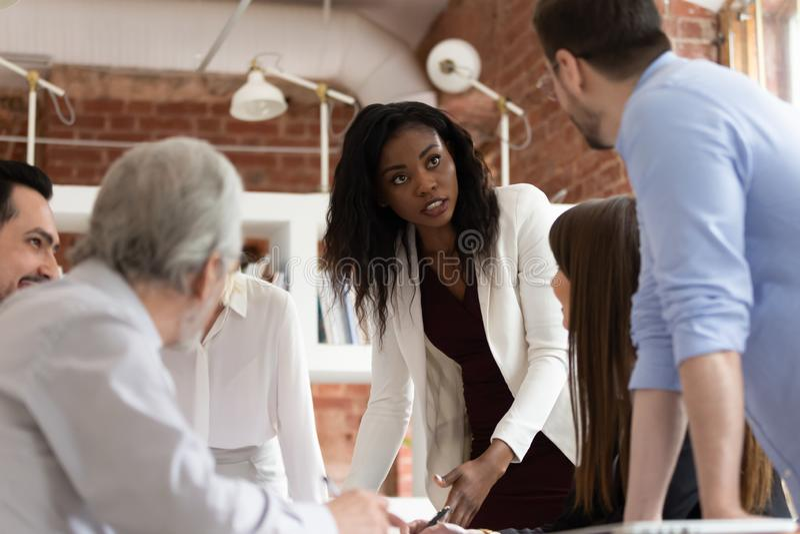 Σοβαρή θηλυκή μαύρη εκτελεστική συζήτηση με τον άνδρα συνάδελφος στην ενημέρωση στοκ φωτογραφία με δικαίωμα ελεύθερης χρήσης