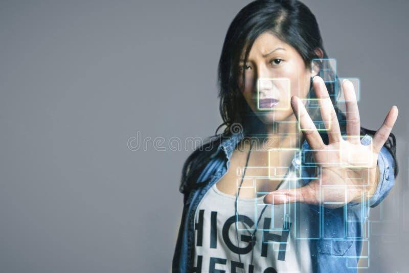 Σοβαρή μέση ενήλικη γυναίκα σχετικά με τη φουτουριστική οθόνη υπολογιστή πέρα από το γκρίζο υπόβαθρο στοκ εικόνες