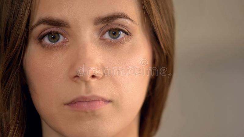 Σοβαρή νέα γυναίκα που εξετάζει τη κάμερα, θύμα οικογενειακής βίας, κινηματογράφηση σε πρώτο πλάνο προσώπου στοκ εικόνες