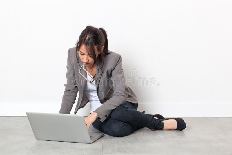 Σοβαρή νέα γυναίκα που εργάζεται στη χαλάρωση lap-top της για την έμπνευση στοκ φωτογραφία