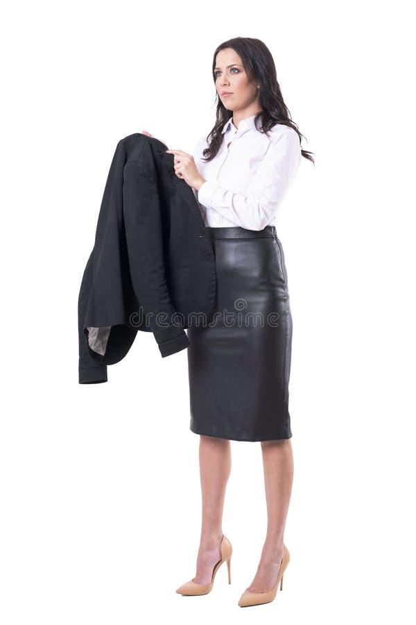 Σοβαρή νέα ενήλικη επιχειρησιακή γυναίκα που αφαιρεί το σακάκι κοστουμιών που κοιτάζει μακριά στοκ φωτογραφία με δικαίωμα ελεύθερης χρήσης