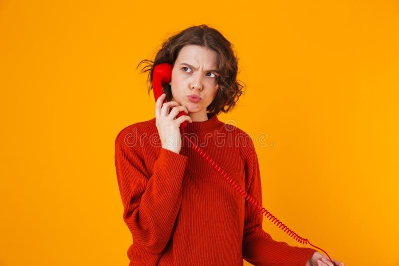 Σοβαρή νέα όμορφη τοποθέτηση γυναικών που απομονώνεται πέρα από το κίτρινο υπόβαθρο τοίχων που μιλά τηλεφωνικώς στοκ φωτογραφία