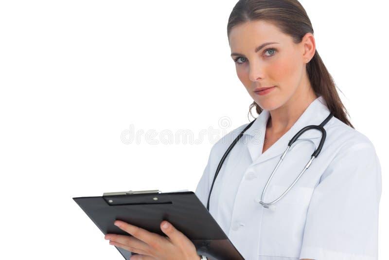 Σοβαρή νοσοκόμα που γράφει στην περιοχή αποκομμάτων και που εξετάζει τη κάμερα στοκ φωτογραφίες