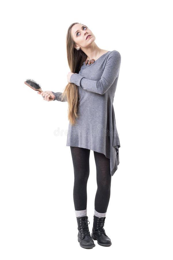 Σοβαρή σκεπτική νέα μοντέρνη γυναίκα που φαίνεται επάνω και που κρατά βουρτσίζοντας την τρίχα της με τη βούρτσα στοκ εικόνες