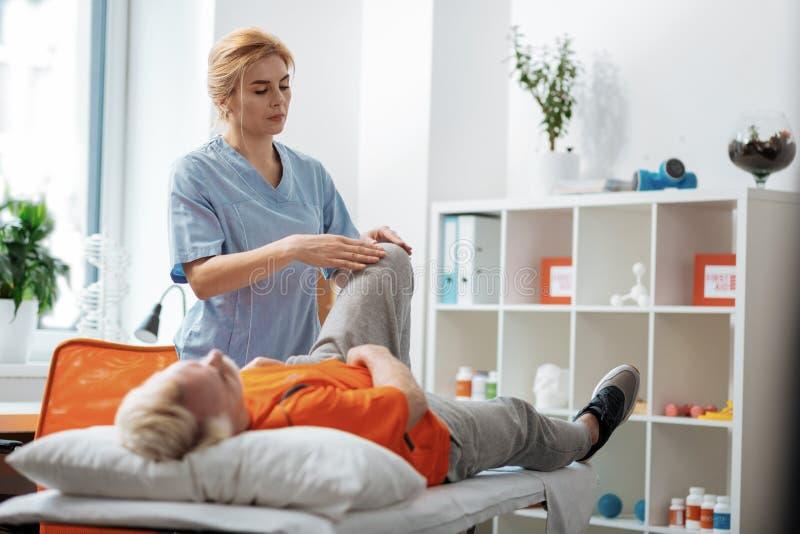 Σοβαρή συμπαθητική γυναίκα σχετικά με το γόνατο ασθενών της στοκ εικόνες