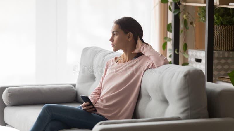 Σοβαρή συνεδρίαση γυναικών στον καναπέ στο καθιστικό με το τηλέφωνο στοκ εικόνα