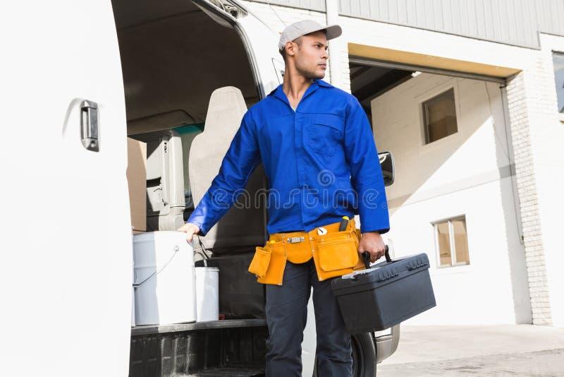 Σοβαρή όμορφη handyman εργαλειοθήκη εκμετάλλευσης στοκ φωτογραφία