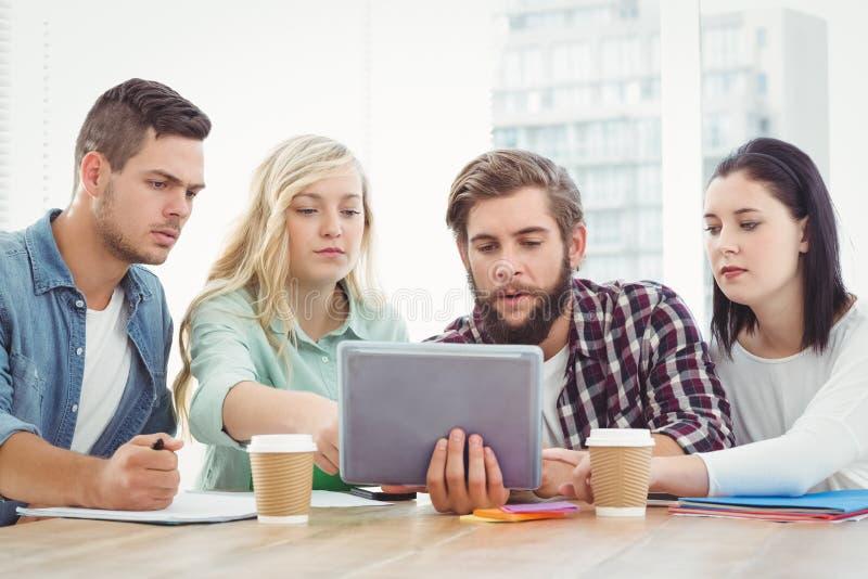Σοβαροί δημιουργικοί επιχειρηματίες που χρησιμοποιούν την ψηφιακή ταμπλέτα στοκ εικόνα