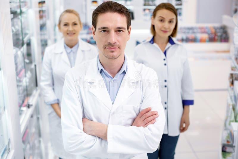 Σοβαροί τρεις φαρμακοποιοί που εργάζονται στο φαρμακείο στοκ φωτογραφίες