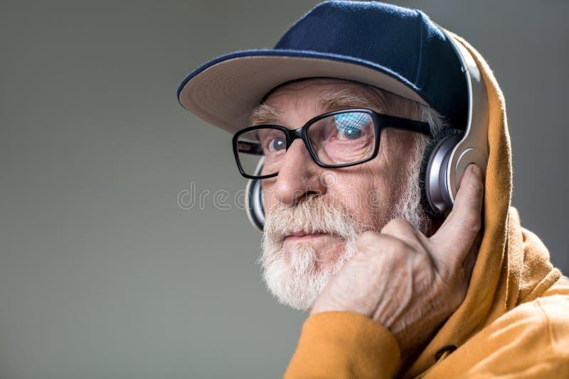 Σοβαρός αξύριστος ηληκιωμένος με τα ακουστικά στοκ εικόνες