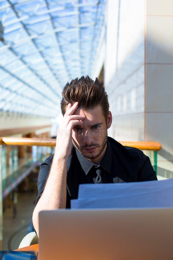 Σοβαρός αρσενικός επιχειρηματίας που ερευνά την περίληψη πρίν συναντά με τους νέους εργαζομένους στοκ φωτογραφίες