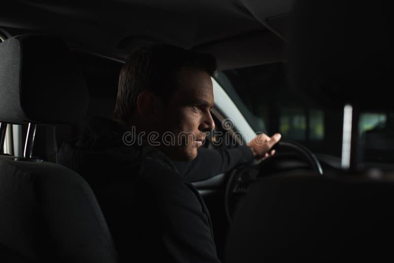 σοβαρός αρσενικός ιδιωτικός αστυνομικός που κάνει την επιτήρηση από στοκ εικόνα