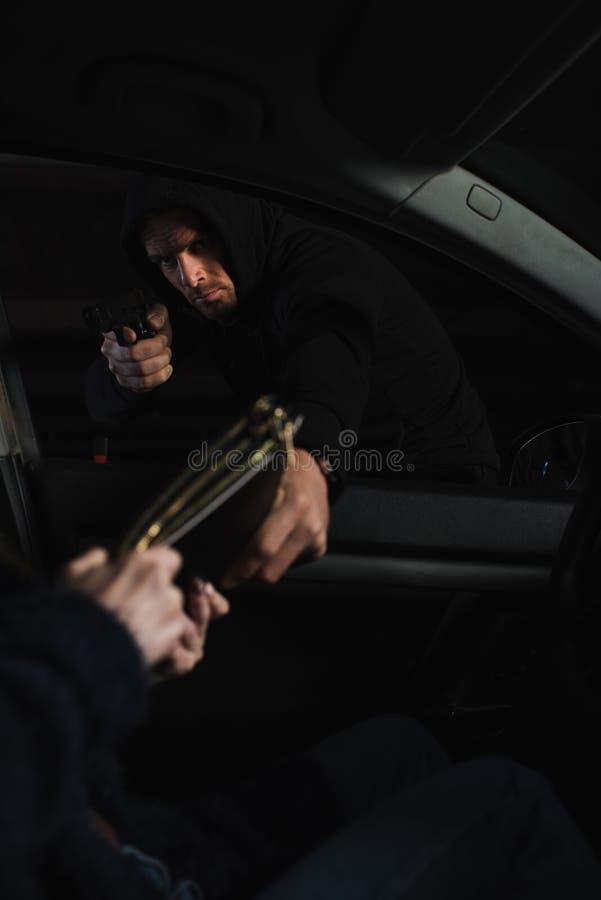σοβαρός αρσενικός κλέφτης που στοχεύει από το πυροβόλο όπλο και τη stealing τσάντα από τη γυναίκα στοκ φωτογραφία