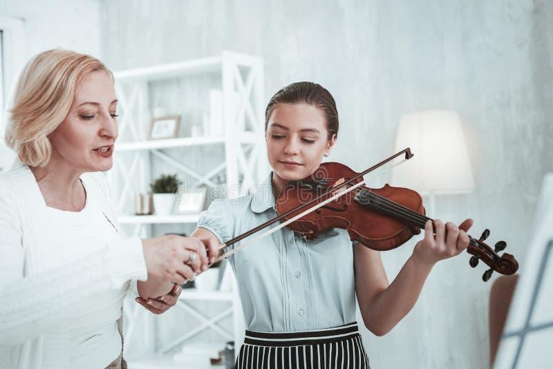 Σοβαρός επαγγελματικός δάσκαλος μουσικής που κρατά ένα τόξο βιολιών στοκ φωτογραφία με δικαίωμα ελεύθερης χρήσης